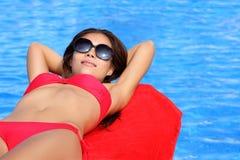 Frau, die durch Pool ein Sonnenbad nimmt Lizenzfreie Stockfotografie