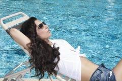 Frau, die durch Pool sich entspannt Lizenzfreies Stockfoto