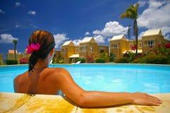Frau, die durch Rand des Pools sitzt Lizenzfreies Stockfoto