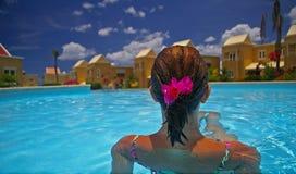 Frau, die durch Rand des Pools sitzt Stockfoto