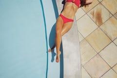 Frau, die durch Swimmingpool ein Sonnenbad nimmt Lizenzfreie Stockfotografie