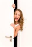 Frau, die durch Tür späht Lizenzfreies Stockfoto