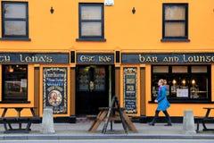 Frau, die durch Tante Lenas, populärer Bar und Aufenthaltsraums, Dorfs von Adare, Irland, im Oktober 2014 geht Stockfotografie