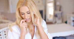 Frau, die durch Telefon beim Beißen ihres Nagels nennt Stockbilder