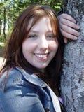 Frau, die durch Tree aufwirft stockfotografie