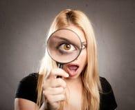 Frau, die durch Vergrößerungsglas schaut stockfotos