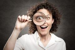 Frau, die durch Vergrößerungsglas schaut Lizenzfreie Stockfotos