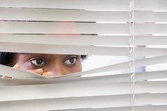 Frau, die durch Vorhänge schaut stockfotos