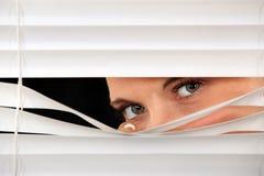 Frau, die durch Vorhänge späht Stockfotografie