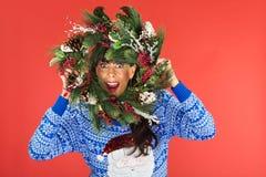Frau, die durch Weihnachtskranz schaut Stockbilder