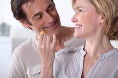 Frau, die Ehemann einen Biskuit gibt lizenzfreies stockbild