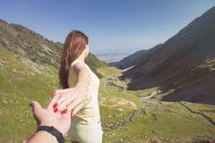 Frau, die eigenhändig Mann auf die Oberseite des Berges hält Lizenzfreies Stockbild