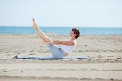 Frau, die Eignungübung auf Strand tut Stockfoto