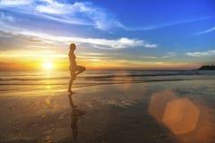 Frau, die Eignung auf dem Ozeanstrand während des erstaunlichen Sonnenuntergangs tut Stockfotografie