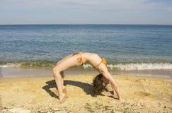 Frau, die Eignung auf Strand macht Stockfoto