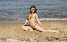 Frau, die Eignung auf Strand tut Stockbild