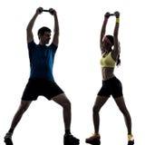 Frau, die Eignungsgewichtstraining mit Manntrainer silhouet ausübt Stockfoto