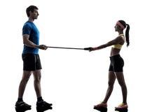 Frau, die Eignungswiderstand-Gummiband mit Manntrainer ausübt Lizenzfreies Stockfoto