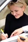 Frau, die ein Abkommen unterzeichnet, um ein Auto zu kaufen Lizenzfreies Stockbild
