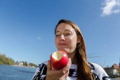 Frau, die ein Apfellachen genießt Stockfotografie