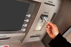 Frau, die ein ATM verwendet Stockbild