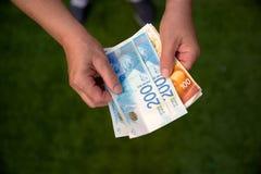 Frau, die ein Bündel israelische neue Schekelbanknoten in ihren Händen hält stockfotos
