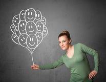 Frau, die ein Bündel lächelnde Ballone hält Lizenzfreie Stockbilder
