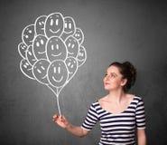 Frau, die ein Bündel lächelnde Ballone hält Lizenzfreie Stockfotos