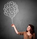 Frau, die ein Bündel lächelnde Ballone hält Stockbilder
