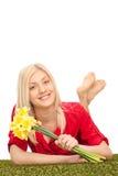 Frau, die ein Bündel Tulpen hält und auf Gras liegt Lizenzfreies Stockfoto
