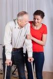 Frau, die ein behindertes hilft, um zu gehen Stockfotos