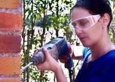 Frau, die ein Bohrgerät verwendet lizenzfreie stockbilder