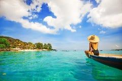 Frau, die ein Boot in einer Paradiesinsel segelt Lizenzfreies Stockfoto