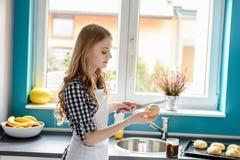 Frau, die ein Brötchen mit Messer in der Küche schneidet Stockbild