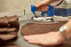 Frau, die ein braunes Material mit einem Eisen auf einem Bügelbrett streicht stockfoto