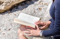 Frau, die ein Buch auf einem Strand liest Lizenzfreie Stockfotografie