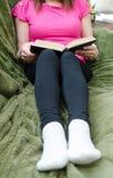Frau, die ein Buch auf einer Couch liest Stockfotos