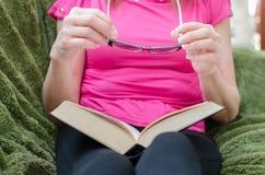 Frau, die ein Buch auf einer Couch liest Lizenzfreie Stockfotografie