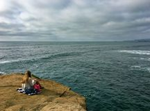 Frau, die ein Buch auf einer Küstenklippe heraus schaut auf den Pazifischen Ozean liest Stockfotos