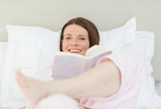 Frau, die ein Buch auf ihrem Bett liest Stockbilder