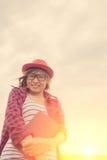 Frau, die ein Buch in den Wiesen auf dem Sonnenschein des Morgens hält Stockfotografie