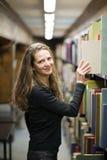 Frau, die ein Buch in der alten Bibliothek nimmt Lizenzfreie Stockbilder