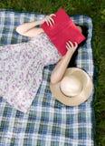 Frau, die ein Buch draußen auf dem Gras liest Stockbilder