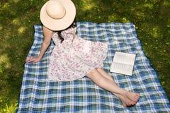 Frau, die ein Buch draußen im Gras liest Lizenzfreie Stockfotos