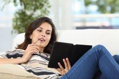 Frau, die ein Buch in einem ebook liest lizenzfreie stockfotos