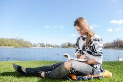 Frau, die ein Buch in einem Park liest Stockfotografie