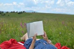 Frau, die ein Buch in einer Landschaft liest Stockfoto