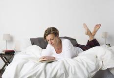 Frau, die ein Buch im Bett liest lizenzfreies stockfoto