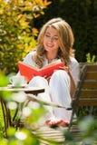 Frau, die ein Buch im Garten liest Stockfotografie