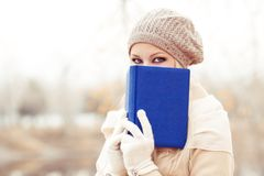 Frau, die ein Buch im Herbstpark liest lizenzfreie stockbilder